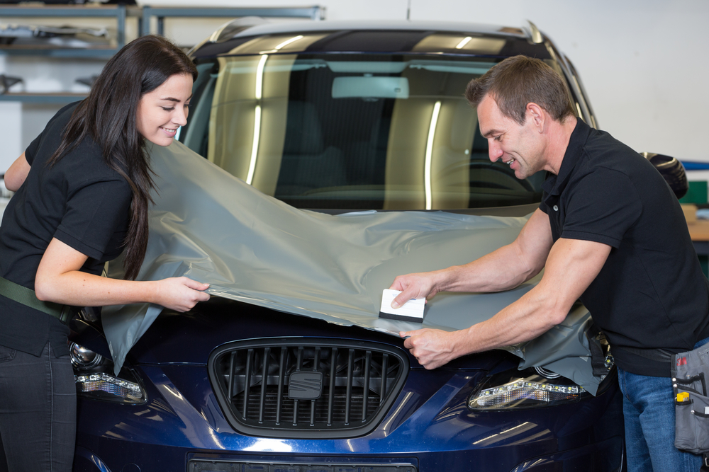 Car wrappers using squeegee to straighten vinyl foil